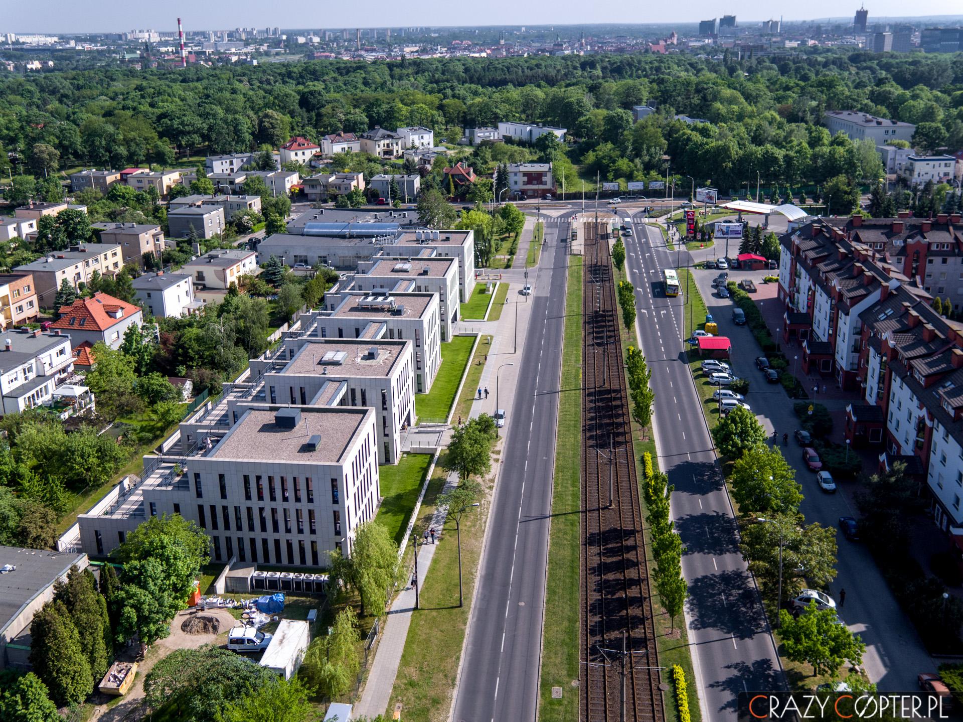 Zdjęcia nieruchomości z drona pokazują nie tylko budynek, ale i atrakcyjne otoczenie. Tutaj linia tramwajowa wraz z przystankiem autobusowym oraz zielenią w postaci parku miejskiego.
